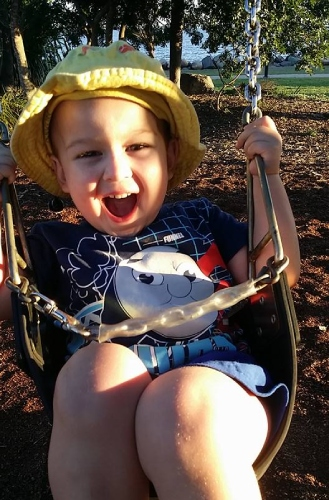 Beautiful boy on a swing in the park at Clontarf
